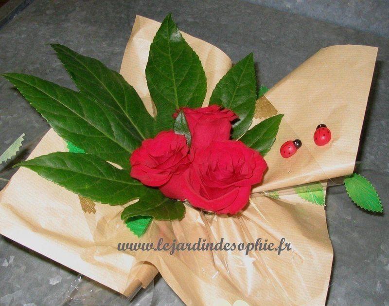 Petites coccinelles autocollantes dans une composition florale de roses rouge