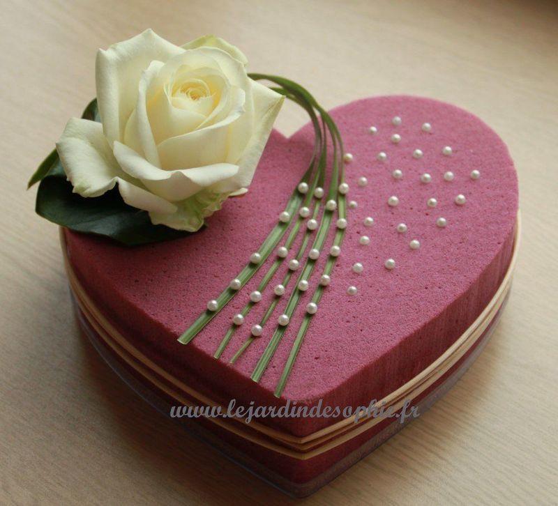 Mise en valeur d'une rose blanche sur une coeur mousse florale couleur
