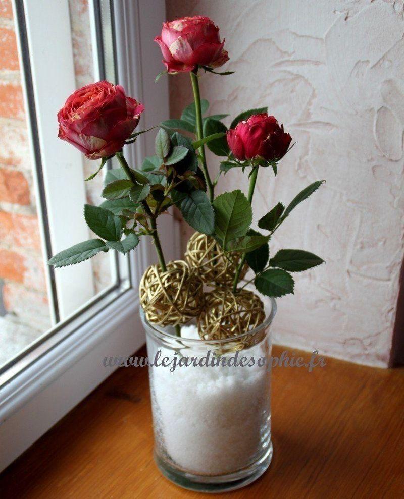 Neige artificielle gonflante dans un vase avec des roses et boules en osier